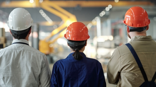 Rear view of manufacturing employees in hardhats standing together and looking at factory machines in workshop